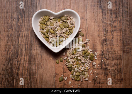 Heart shaped bowl with mixed nuts and seeds - Stock Photo