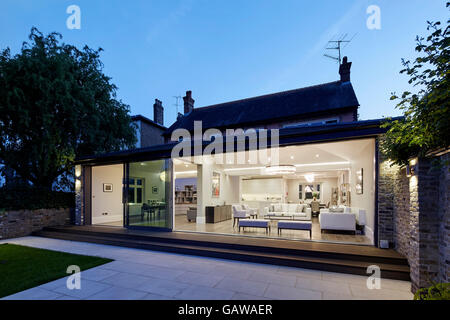 Twilight view from garden towards lit up extension interior. Private House, Highlever Road, London, United Kingdom. - Stock Photo