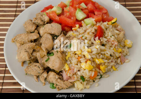 pork with egg fried rice and mixed salad on a plate - Stock Photo