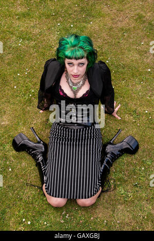 A woman fashionable kneeling on the grass wearing high-heels boots and wearing an Alice In Wonderland style outfit - Stock Photo