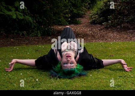A woman wearing an Alice In Wonderland style outfit lying on the grass sleeping inside the Botanical Gardens in - Stock Photo