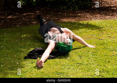 A woman wearing an Alice In Wonderland style outfit rolling on the grass inside the Botanical Gardens in Dundee, - Stock Photo
