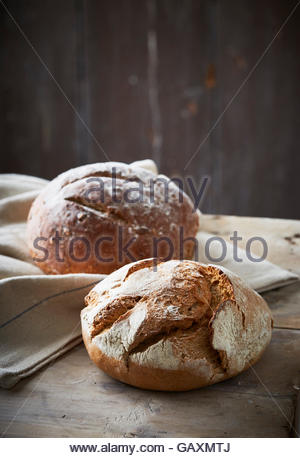 two artisan baked loaves on dark background with linen cloth - Stock Photo