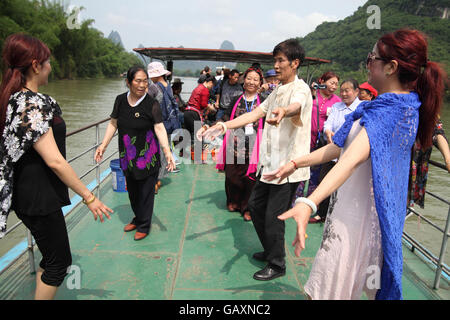 People of a Tibetan family, tourists, dance a Tibetan dance on a cruise boat with other tourists around. River Li - Stock Photo
