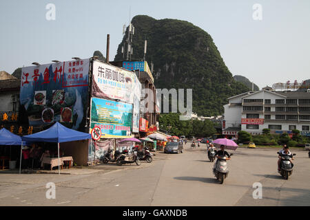 Motorbikes and bicycles riding on a street, in the background we see the Guilin area Karst hills and billboards - Stock Photo