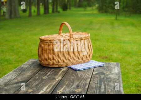 Picnic basket with blue white checkered tablecloth on wooden table. Summertime park lawn in the background - Stock Photo