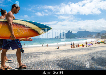 RIO DE JANEIRO - APRIL 3, 2016: Young carioca Brazilian couple walks with surfboards Arpoador, the popular surf - Stock Photo
