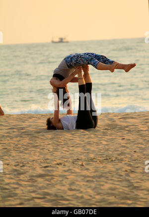 Two young women performing acro yoga on the beaches of Goa, India - Stock Photo