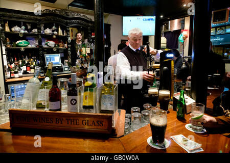 Bartender pouring a pint of beer at The Old Stand pub in Dublin, Republic of Ireland, Europe - Stock Photo