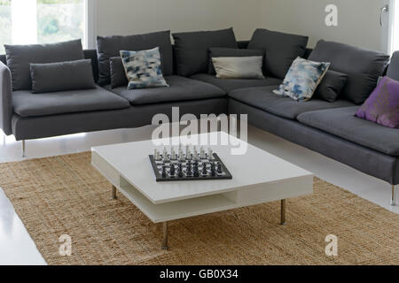 Living room with a big L shaped sofa and a chess board on the center table - Stock Photo