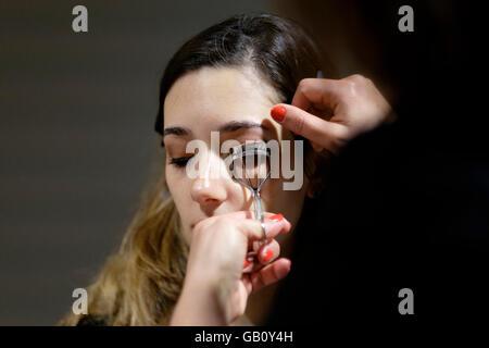 Professional make up artist using eyelash curler on client - Stock Photo