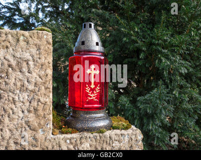 Red grave lantern with golden cross - Stock Photo