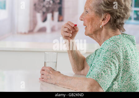 happy senior woman with pills glass of water at home - Stock Photo