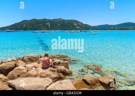 Unidentified young woman relaxing on Santa Giulia beach, Corsica island, France - Stock Photo