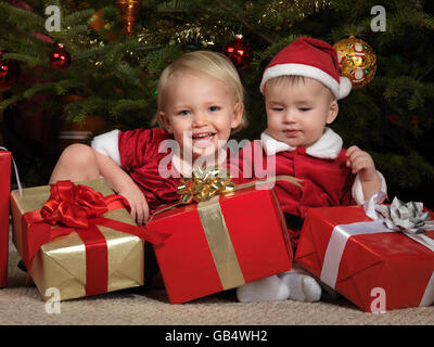 Two year old girl and an eight month old boy sitting with presents under a Christmas tree - Stock Photo