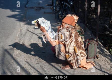 Unidentified sadhu sitting on the road. - Stock Photo