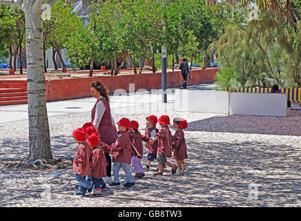 LISBON, PORTUGAL - JUNE 16, 2015: Group of children with uniforms and their teacher going for a walk near the Lisbon - Stock Photo