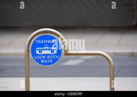 Tramway Look Both Ways warning sign on the edge of the tram tracks on the promenade in Blackpool, Lancashire, UK - Stock Photo