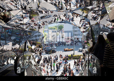 People ride the escalator at the entrance to Tokyu Plaza on Omotesando, Harajuku, in Tokyo, Japan. - Stock Photo