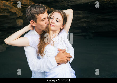 Happy family on honeymoon holiday - just married young man and woman hug with smile on black sand beach with rock background. Ac Stock Photo