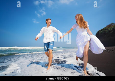 Happy family on honeymoon holiday - just married young man and woman run with fun by black sand beach along sea - Stock Photo