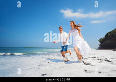 Happy newlywed family on honeymoon holiday - just married loving couple run with fun by black sand beach along sea - Stock Photo