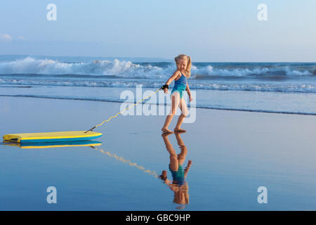 Little baby girl - young surfer with bodyboard has fun on sea beach. Family lifestyle, people water sport activity, - Stock Photo