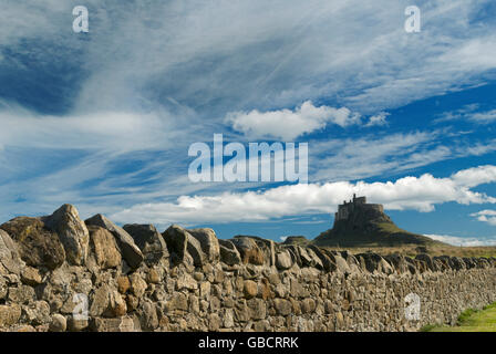 Lindisfarne Castle on Holy Island, Northumberland, under blue sky with light cloud, with a dry-stone wall - Stock Photo