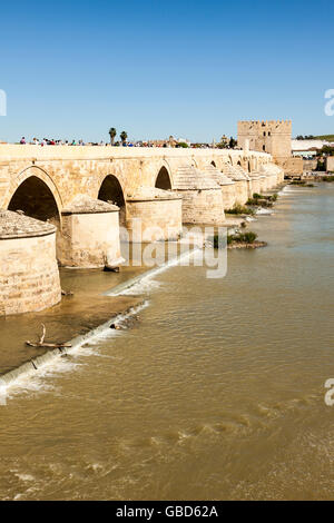 Hundreds of tourists on the ancient roman bridge crossing Guadalquivir river at Córdoba, Andalusia, Spain - Stock Photo