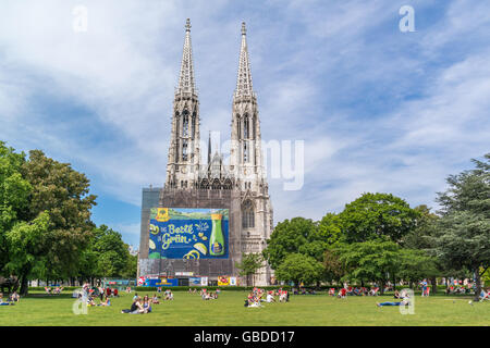 People relaxing in Sigmund Freud Park and Votive Church at Ringstrasse in inner city of Vienna, Austria - Stock Photo