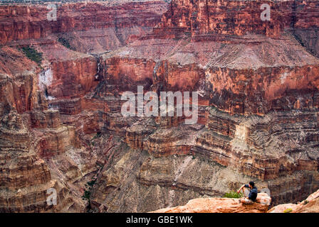 Hiker looking at Grand Canyon from Toroweap Point, 1000 meters above Colorado River, Arizona, USA - Stock Photo