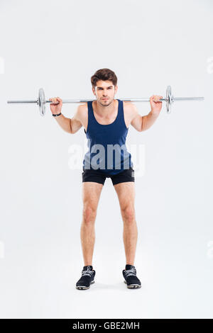 Serious young man athlete standing and exercising with barbell over white background - Stock Photo