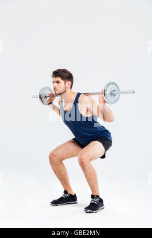 Handsome young man athlete doing squats with barbell over white background - Stock Photo