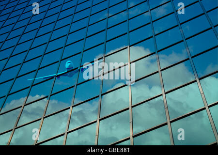 airplane reflect on a glass curtain wall with blue cloudy sky - Stock Photo
