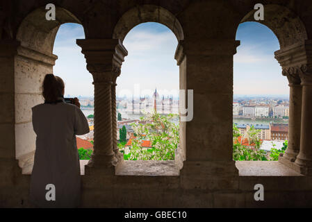 Woman taking photo, a tourist standing in a cloister in the Fishermens Bastion in Budapest photographs the Parliament - Stock Photo