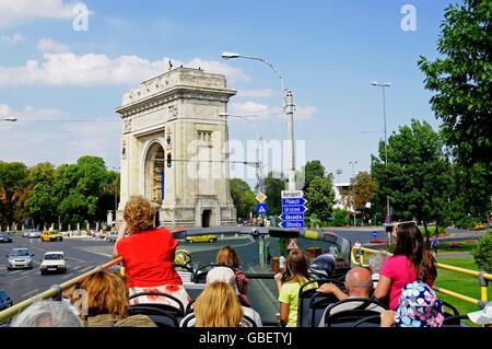 Tourist bus, city tour, Triumphal Arch, Bucharest, Romania - Stock Photo