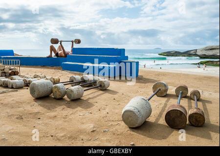 RIO DE JANEIRO - FEBRUARY 12, 2015: Brazilian man exercises at the outdoor workout station at Arpoador. - Stock Photo