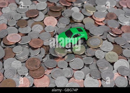 Motoring / car costs concept. Small toy car on top of a pile of randomly spread UK coins as a metaphor for car tax, - Stock Photo