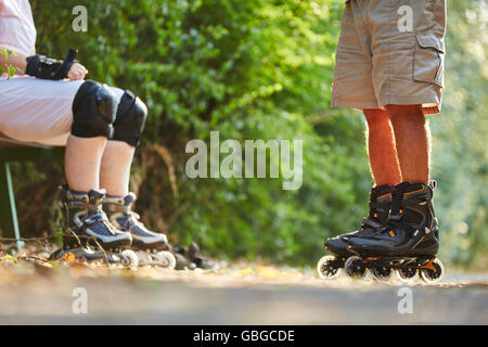 Seniors taking a break from skating with rollerblades in the park - Stock Photo
