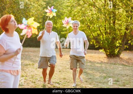 Seniors having fun in the park and holding pinwheels - Stock Photo