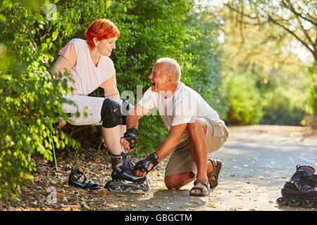 Senior couple laughing and getting ready to skate in the park in summer - Stock Photo