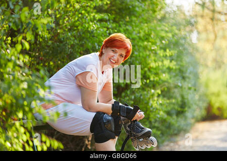 Senior woman taking a break from skating in the park - Stock Photo