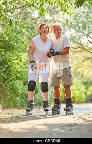 Senior couple inline skating in the park and having fun - Stock Photo