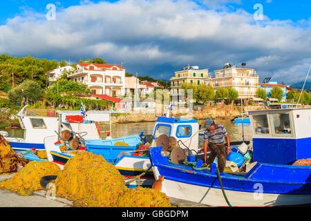 Unidentified fisherman working on Greek fishing boat at sunrise in small port, Samos island, Greece - Stock Photo