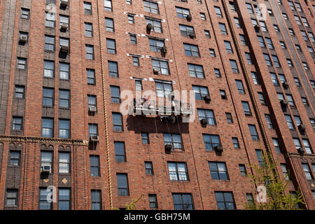 Men on a window cleaning platform hanging off the side of the London Terrace Gardens building in New York, USA, - Stock Photo