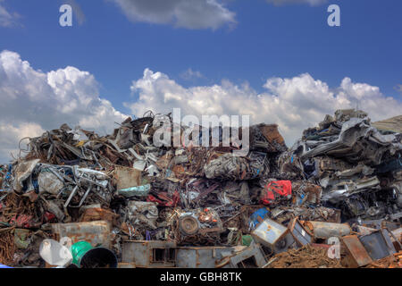 Iron Raw Materials Recycling Pile over Cloudy Sky - Stock Photo