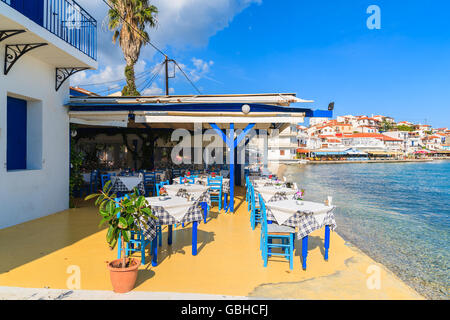 KOKKARI, SAMOS ISLAND - SEP 25, 2015: Tables with chairs in traditional Greek tavern in Kokkari town on coast of - Stock Photo