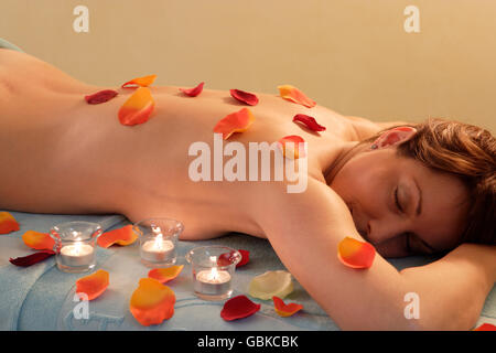 Woman, 35, wellness, relaxing with petals and tea lights