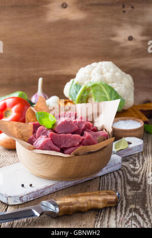 Raw veal cut into pieces with vegetables and other ingredients ready to cook on wooden rustic table, organic cooking - Stock Photo
