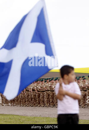 A boy waives the Scottish flag as members of 45 Commando Royal Marines, who recently returned from a tour of duty - Stock Photo